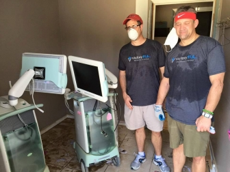 Community volunteers stand beside two of the three destroyed ultrasound units at Care Pregnancy Clinic