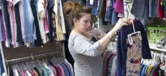 Mackenzie Scott, of Adamstown, holds her 7-month-old daughter, Charlee, while she shops for children's clothing recently at Care Net Frederick.