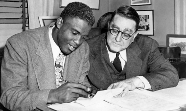 Jackie Robinson signing his initial contract with the Brooklyn Dodgers, alongside general manager Branch Rickey.