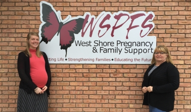 Heather Bush (L) and Barb Hernandez in front of the new sign for West Shore Pregnancy & Family Support.