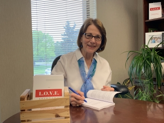 Peggy Hartshorn with her book The L.O.V.E. Approach