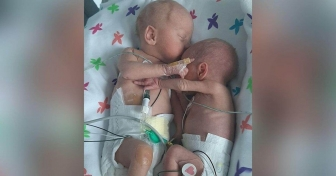 Premature twins separated at birth cuddle and hold hands