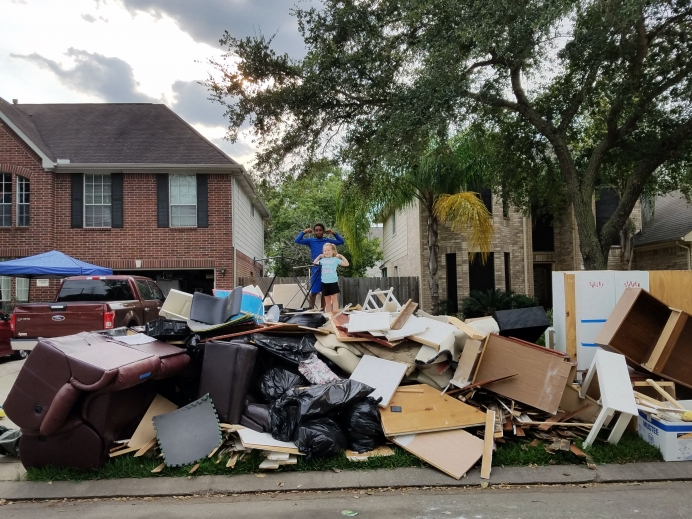 Debbie Simmons' oldest grandchild and youngest child atop the rubble of the Simmons' home following Hurricane Harvey.
