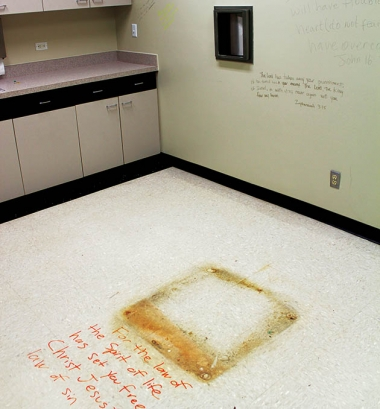 Former abortion procedure room where pro-life advocates have inscribed the walls and floor with Scripture. The floor stain marks the location of the surgical table and the steel carousel in the wall transferred the aborted fetus to the biohazard waste.